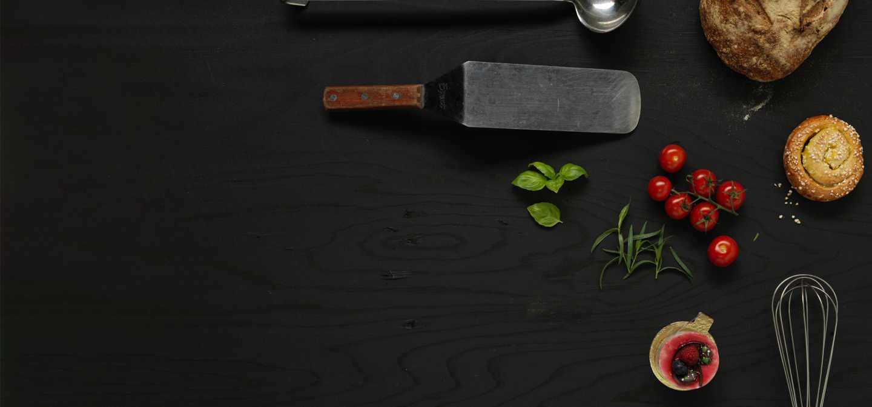 Bild representerande programmet restaurang och livsmedel med en köksspade, tomater, kryddor, bulle, bröd och en söt bakelse.