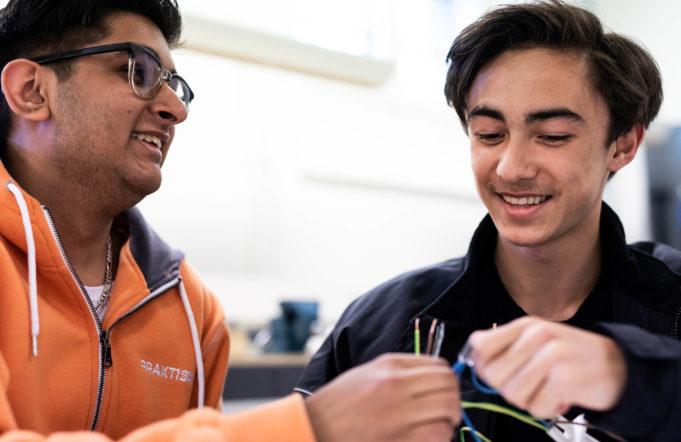 Två elever ler och arbetar med sladdar