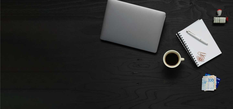 Bild representerande programmet handel och administration med en laptop, anteckningsblock, en kaffekopp och sedlar med pengar