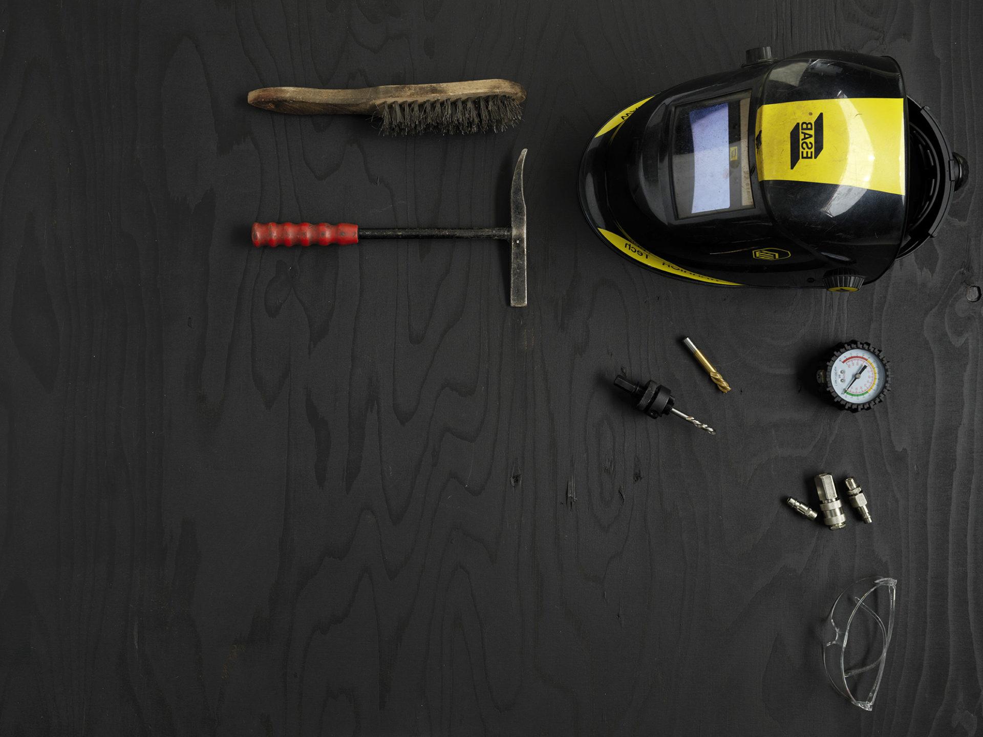 Bild representerande industriprogrammet med en skyddshjälm, skyddsglasögon, borste och en mätare
