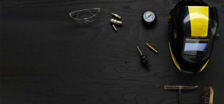 Bild representerande industriteknik med heltäckande skyddsmask, skyddsglasögon, mätare och skruvar