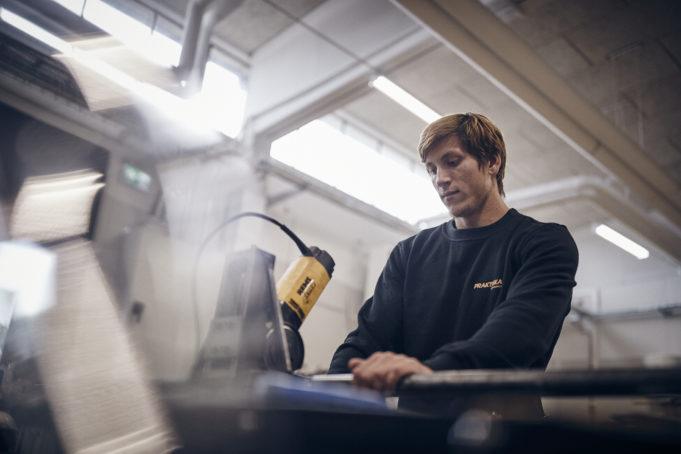 En elev står och arbetar framför en VVS-relaterad maskin