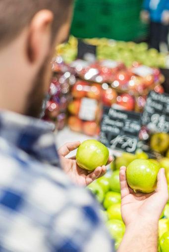 En bild från en persons axel, i fokus är två gröna äpplen personen håller i. Bakom äpplena är andra frukter i fokus.