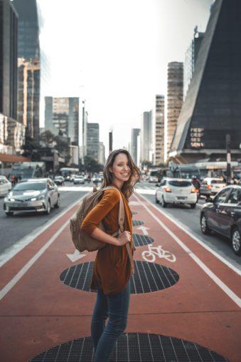 En bild på en tjej som står på en gatan mitt i storstad, bilar kör förbi på vänster och höger sida. Hon har en ryggsäck och ler mto kameran
