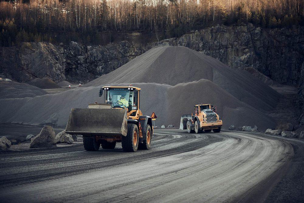 Bild på två grävmaskiner i en backe