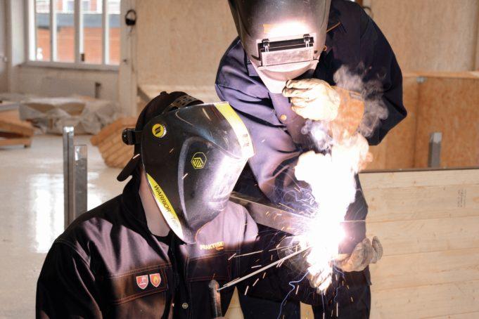 Två personer arbetar med nån form av metall. En person sitter och en person står, båda har en heltäckande skyddsmask och skyddskläder. En glöd lyser.
