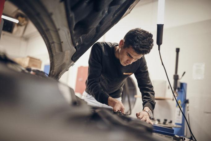 bild på kille som arbetar med en bil