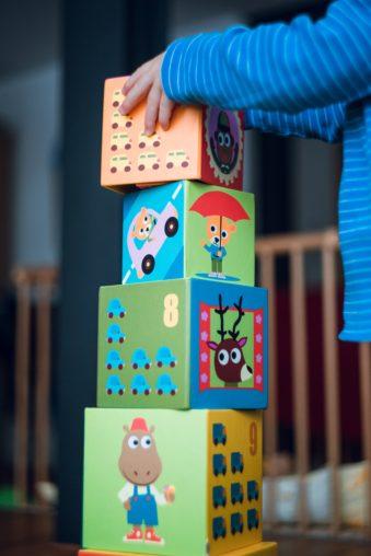 Ett barn bygger klossar med olika motiv på de.